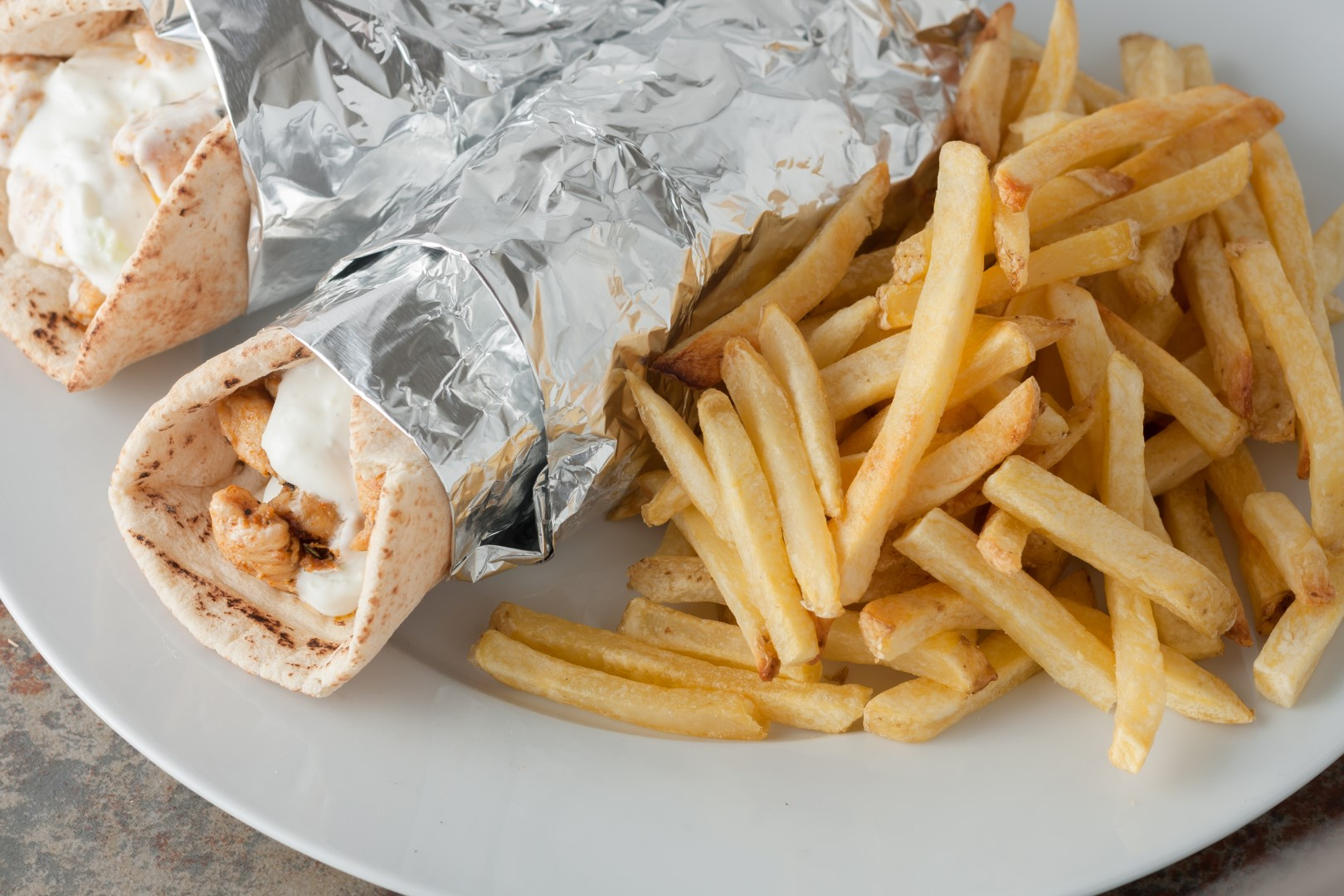 traditional greek food, souvlaki also known as gyros with meat and homemade tzatziki sauce with french fries on white plate